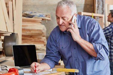 starszy pan pracuje i rozmawia przez telefon